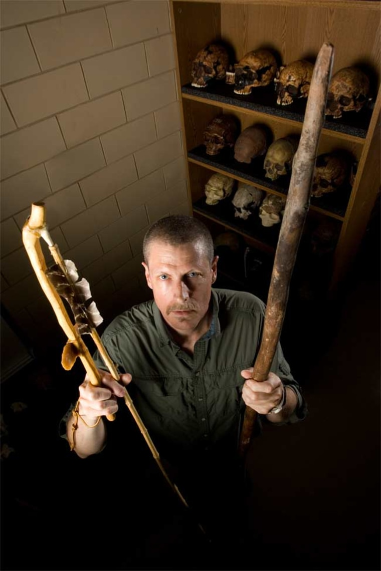 Steven Churchill of Duke University is holding a replica of a Neanderthal-type spear (left hand) and a spear thrower and dart (right hand) that would have been similar to weapons used by early modern humans tens of thousands of years ago.