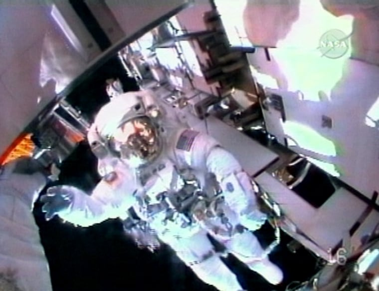 NASA astronautChristopher Cassidy waves while in view of crewmate Dave Wolf's helmet-cam during Wednesday's spacewalk at the international space station. The spacewalk ended early because of rising carbon dioxide levels in Cassidy's suit.