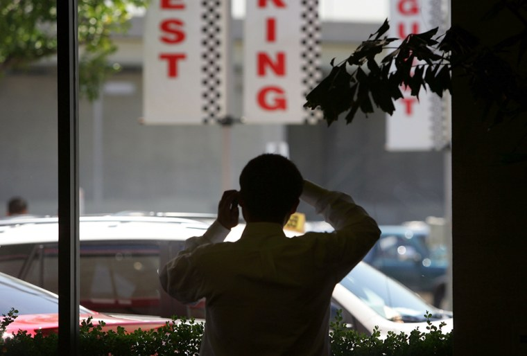 Image: A man talks on a cell phone as he looks at new cars through a window