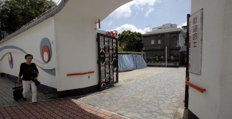 Image: A woman walks past a motel, former home of the late kung fu star Bruce Lee, in Hong Kong's Kowloon Tong district