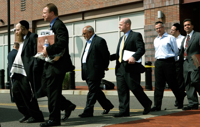 Image: A group of men in custody walk outside the Newark, NJ FBI office.