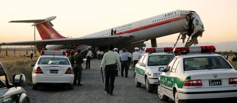 Image: crews clean up after a Iranian jet crash