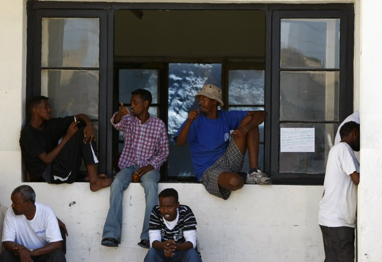 Image: African immigrants and refugees sit on a window sill after a protest outside Valletta