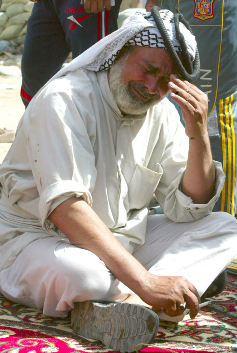 Image: Man reacts upon hearing news of deaths of his friends who were killed in car bomb attack in Baghdad's Shaab District