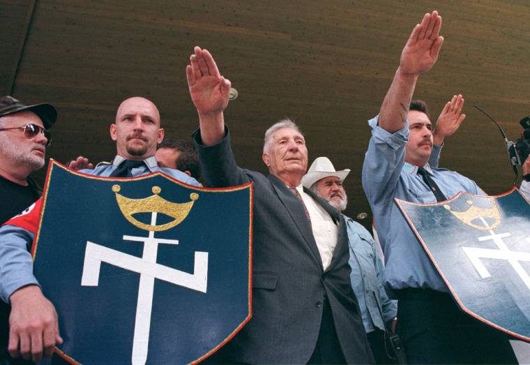 Image: Richard Butler, center, founder of the Aryan Nations sect, salutes along with other members of the neo Nazi group during a rally in Coeur d' Alene, Idaho
