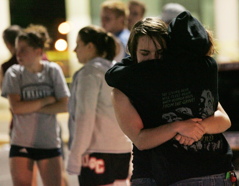 Image: Two women hug in the parking lot outside the LA Fitness gym in Bridgeville after a shooting