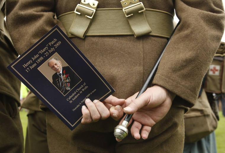 Image: A man dressed in uniform holds an order of service during the funeral of Harry Patch, outside Wells Cathedral, in western England