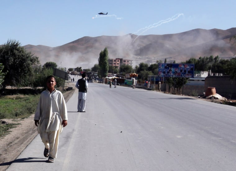 Image: A boy walks away from the site where Taliban are holding a building