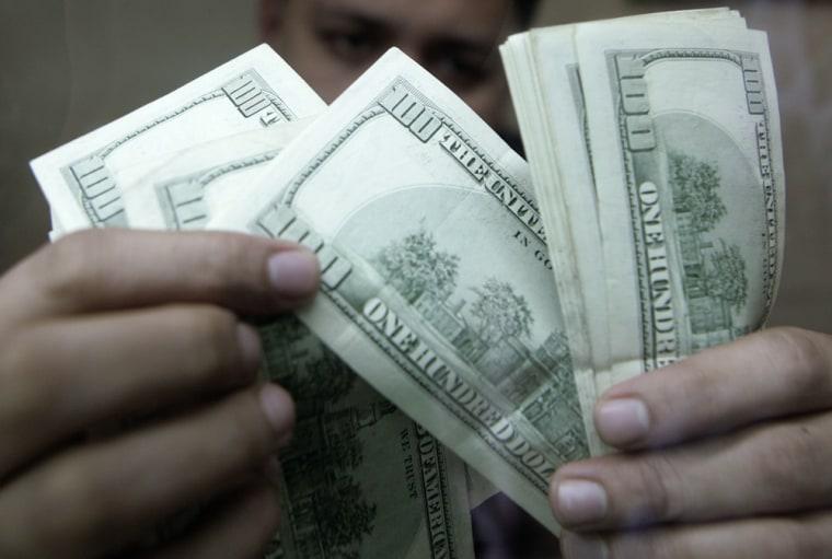 An employee checks dollar bills inside a money changer in Manila