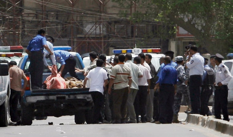 Image: Iraqi police load victims killed in a bank robbery into a truck in central Baghdad, Iraq