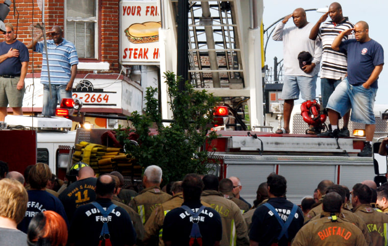 Image: Frefighters salute as they remove bodies of fellow firefighters from a building after a fire