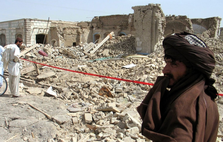 Image: Afghan men look at the destruction caused by a bomb blast