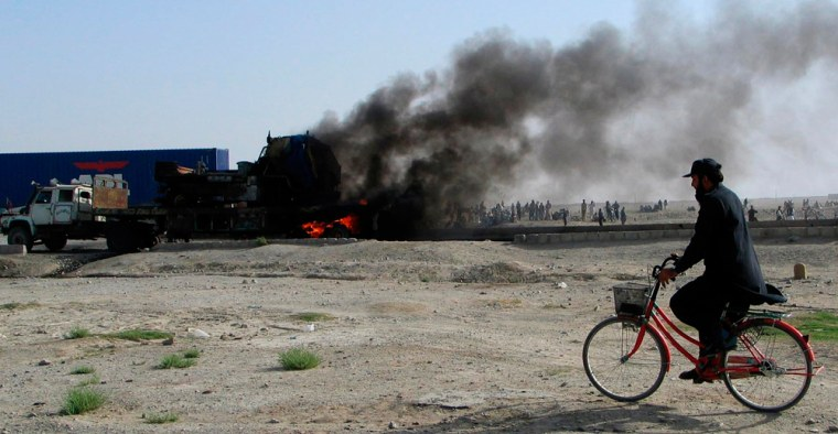 Image: A man rides his bicycle past burning vehicles along the Chaman Pakistan-Afghanistan border