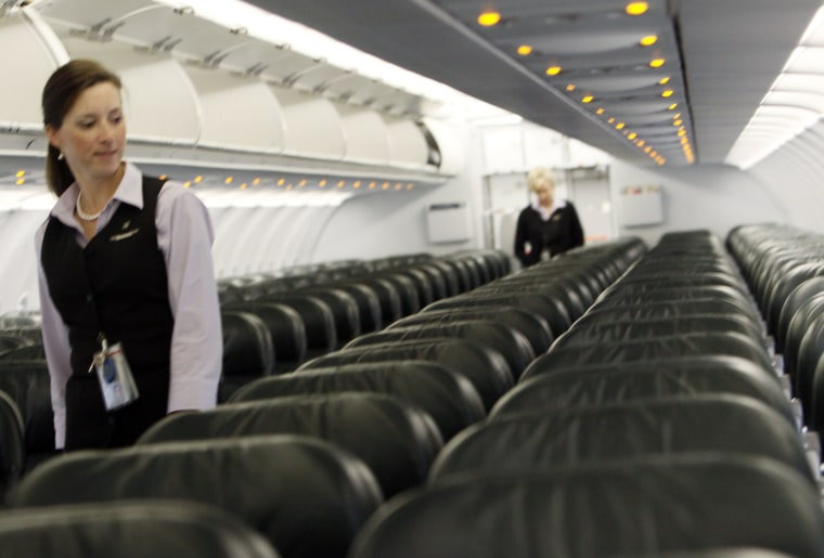 Image: Frontier Airlines flight attendant Cheryl Jacquot checks seats for safety cards before a trip to Washington, DC at the Denver airport
