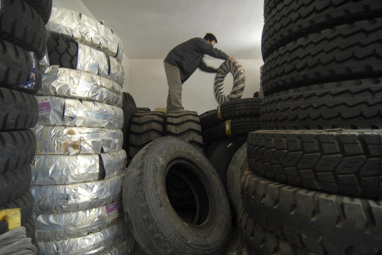 Image: An employee moves tires at a tyre shop in Baokang