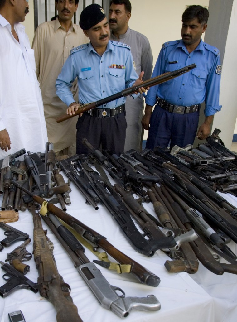 Image: Pakistani police officer inspects confiscated weapons