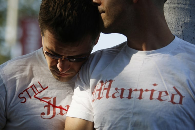 Image: Gay couple Ethan Collings and his spouse Stephen Abate hug