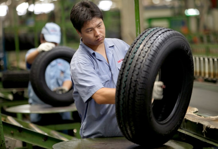 Image: Workers of the Beijing Capital Tire factory check tires as part of quality control procedure