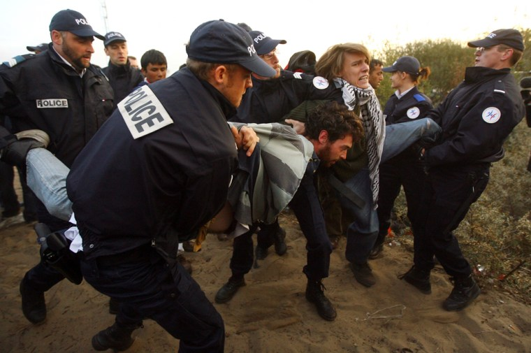 Image: French police officers remove migrants and protesters from the makeshift migrant camp known as 'The Jungle'