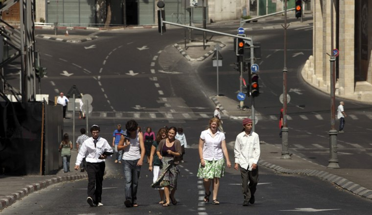 Image: People walk along an empty street during the Jewish holiday of Yom Kippur in Jerusalem