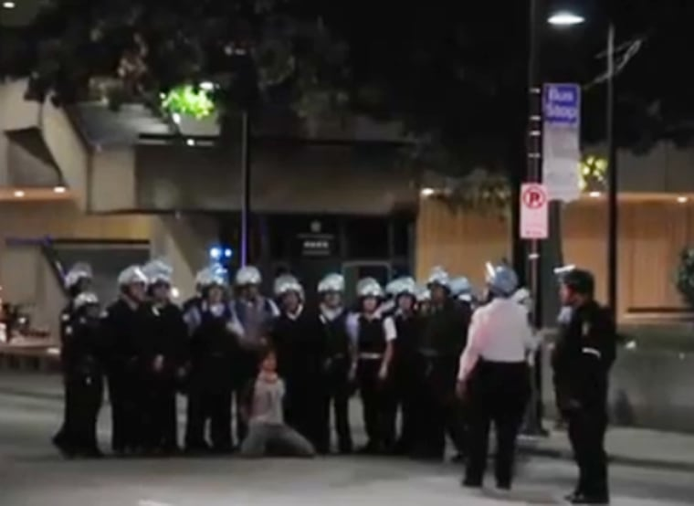 A video posted on YouTube apparently shows about 15 police officers in riot gear posing for a photo with a man they detained kneeling in front of them.