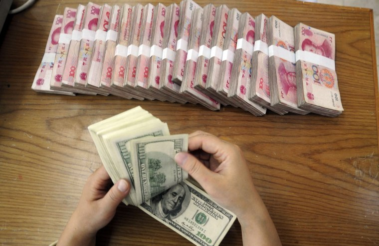 Image: An employee counts U.S. dollar banknotes at a Bank of China branch in Hefei