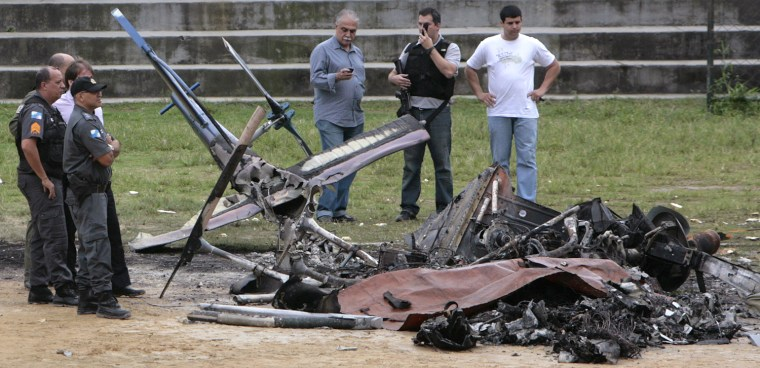 Image: Police inspect the remains of one of their crime-fighting helicopters lying in a soccer field after it was shot down in Rio de Janeiro