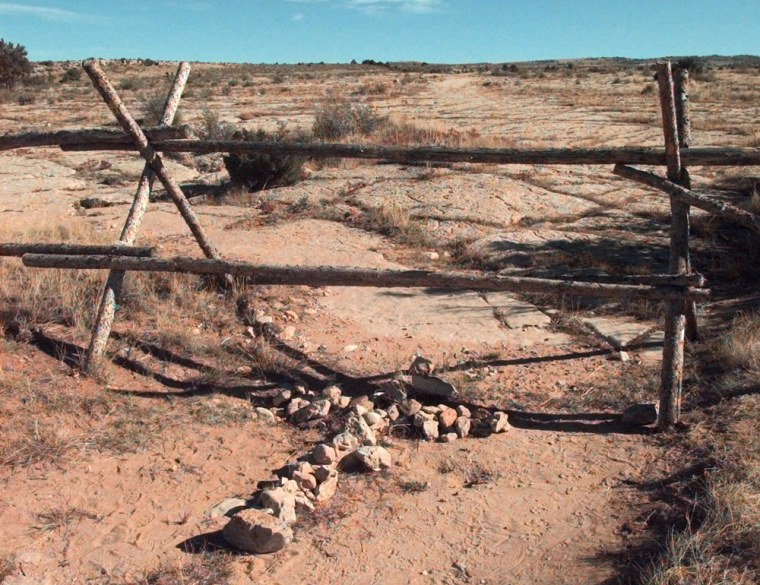 Image:  A cross made of stones rests below the fence in Laramie, Wyoming