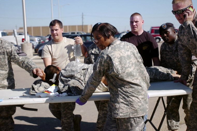 Image: U.S. Army first responders use a table as a stretcher to transport a wounded soldier to an awaiting ambulance at Fort Hood