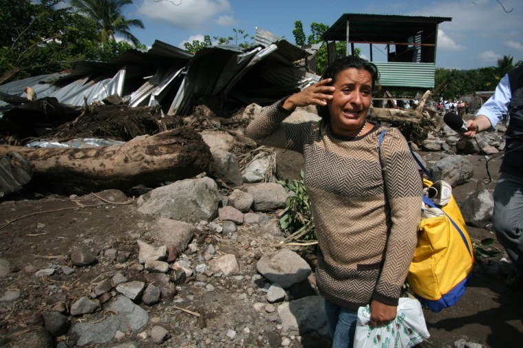 Image: A woman stands in front of her home that was destroyed during flooding in Verapaz, El Salvador,