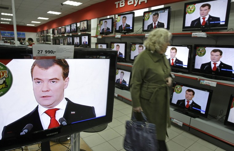 Image: A woman looks a display with TV sets broadcasting Russian President Dmitry Medvedev's address to the nation