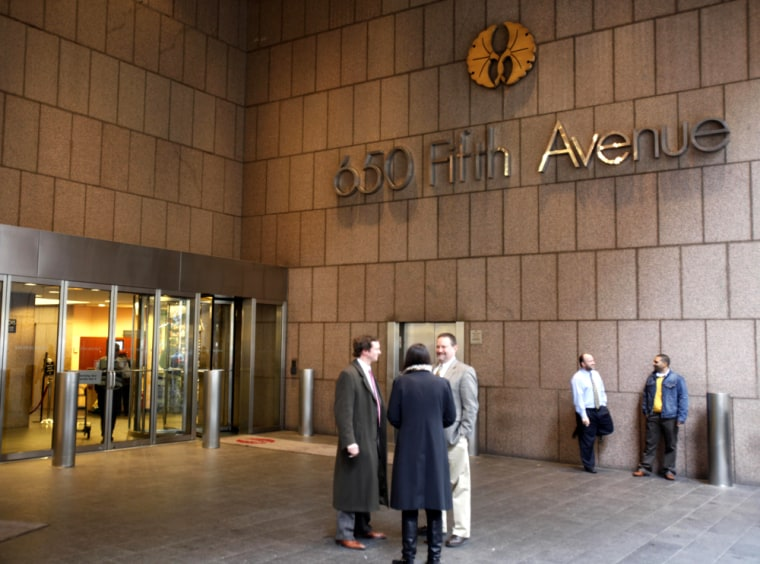 Image: People stand near an entrance to 650 5th Ave in New York