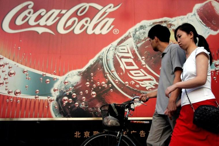 Image: couple walks by Coca-Cola sign
