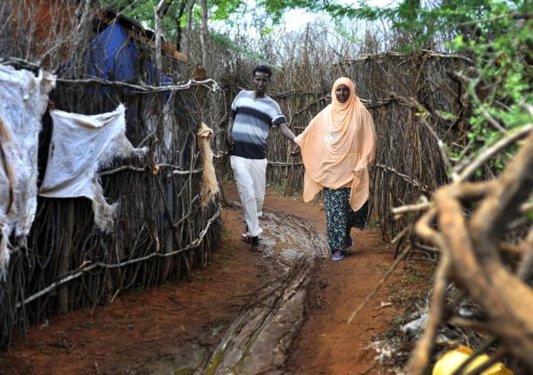 Image: Fatuma Mohamed and her son Ahmedweli walking in a refugee camp, in Dadaab eastern Kenya
