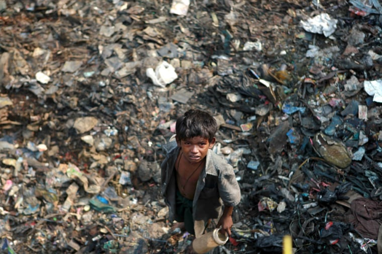 Image: A street child stands on a pile of garbage in Mumbai, India.