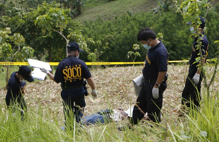 Image: Police investigators inspect the scene of a massacre on the outskirts of Ampatuan