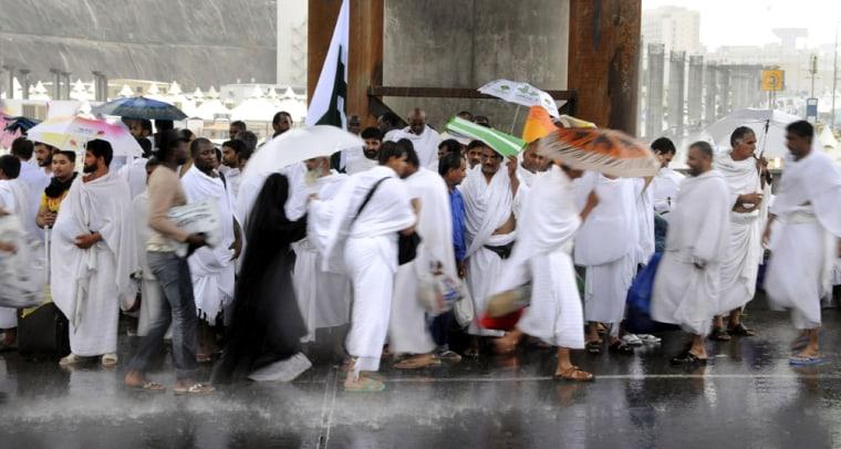 Image: Pilgrims attending the hajj shelter from heavy rains