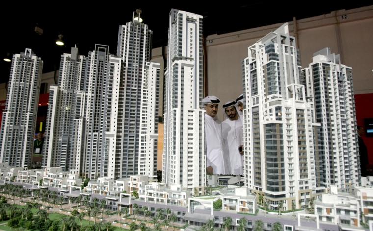 Image: Emirati men look at models of buildings