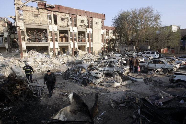 Image: People walk at the site of destroyed building and vehicles, a day after a bomb attack in central Baghdad