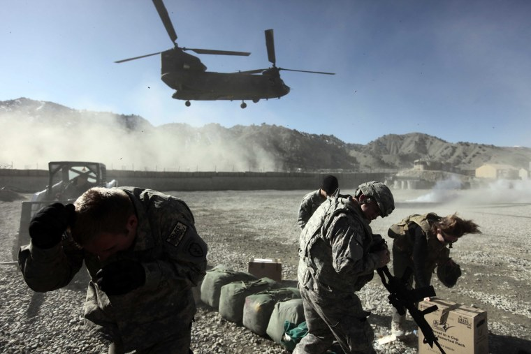 Image: U.S. army soldiers shield themselves from swirling dust generated by a Chinook CH-47F transport helicopter in Paktya province