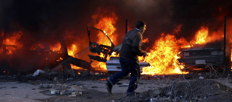 Image: A resident runs from the site of a bomb attack as fire engulfs vehicles in central Baghdad