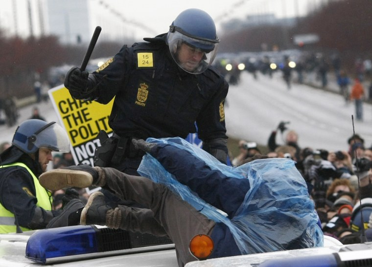 Image: A police officer beats a protester at a road block during a demonstration outside the United Nations Climate Change Conference 2009 in Copenhagen