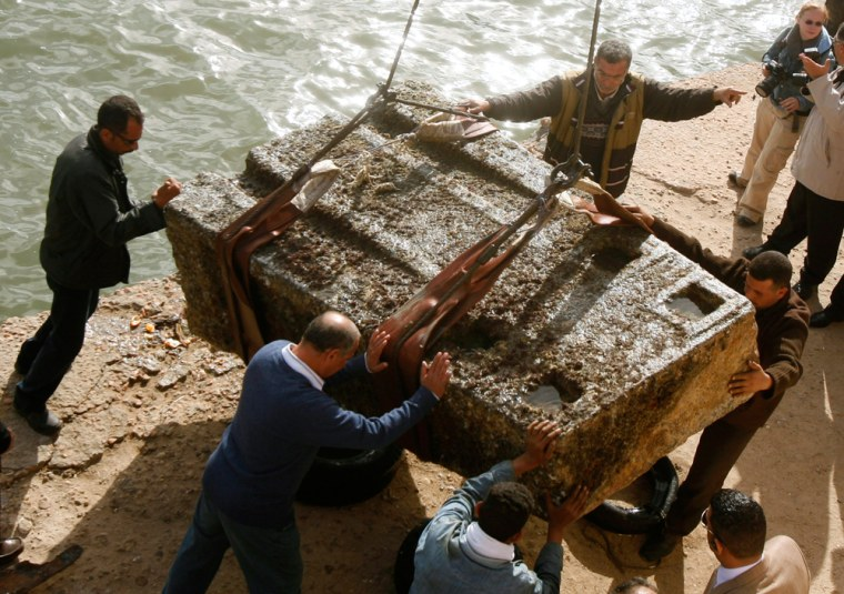 Image: Workers handle an ancient Egyptian granite tower that was retrieved from the Mediterranean Sea, at Alexandria's eastern harbour