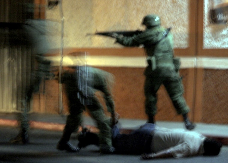 Image: Mexican soldiers detain an unidentified man during a navy operation in Cuernavaca