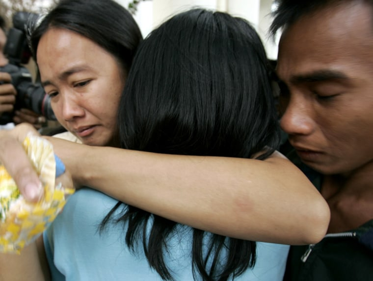 Image: Relatives embrace after a ferry collided with a fishing boat