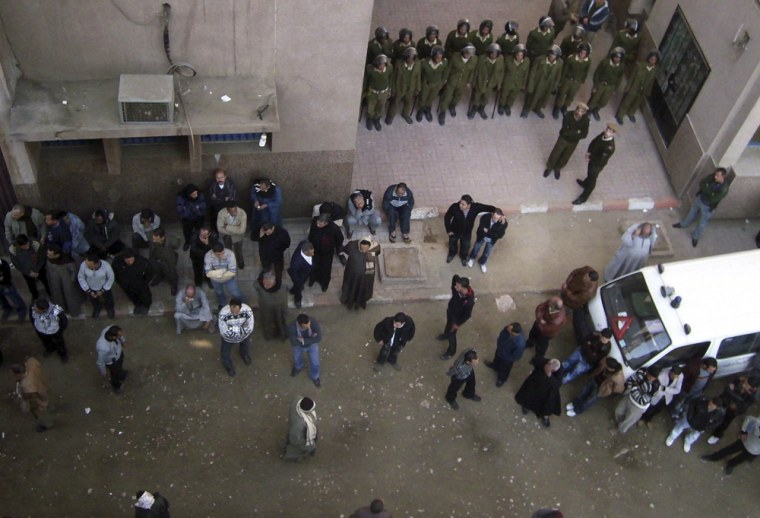 Image: Egyptian relatives of the injured and soldiers are seen outside Nag Hamadi hospital