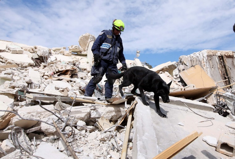 Image: Christopher Holmes from the Fairfax County Urban Search and Rescue searches for survivors in the rubble of a building