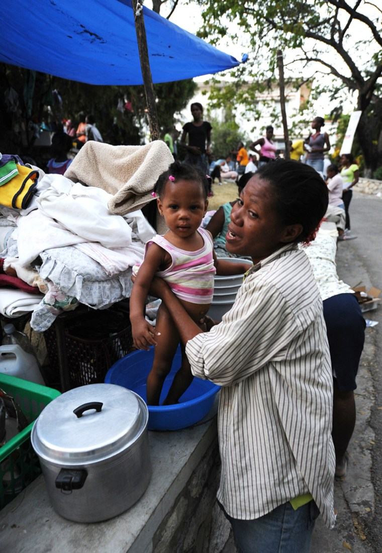 Image: woman bathes her daughter in a temporary camp