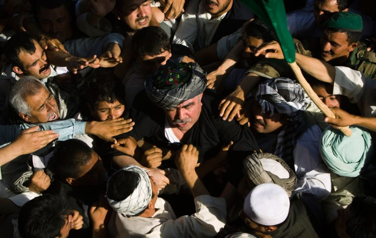 Image: A crowd welcomes Afghan General Dostum from exile in Turkey during a ceremony in Shibergan