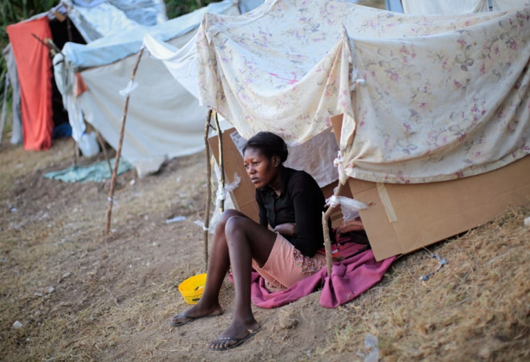 Image: A woman sits at her tent at a makeshift camp in Port-au-Prince, Haiti